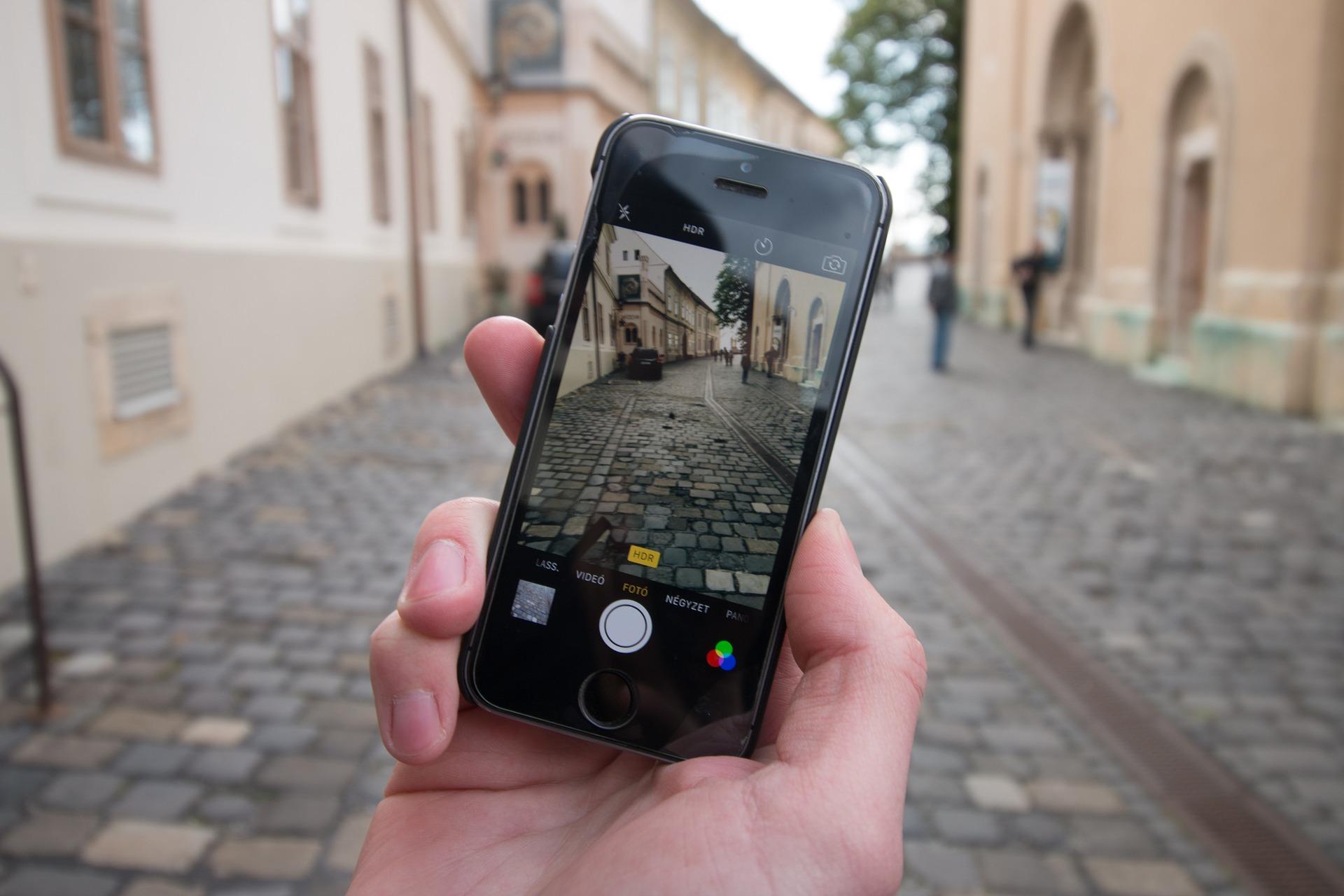 Imagem de uma pessoa segurando um celular em frente a uma rua. Na tela do celular aparece uma imagem dessa mesma rua smart city